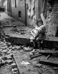 17-Little-girl-with-her-doll-sitting-in-the-ruins-of-her-bombed-home-London-1940